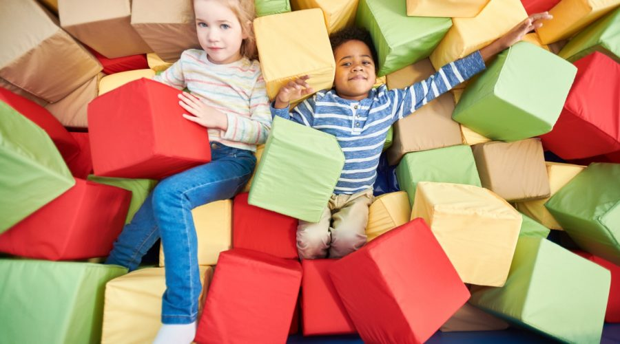 Colorful above view portrait of two happy little kids playing in foam pit of trampoline center, copy space